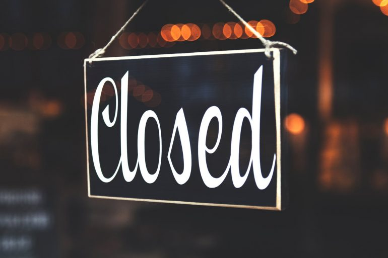 A closed sign stands out in front of a bokeh background