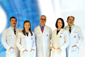 Spectrum Optical's Optometrists stand together, smiling, in front of a blurred blue and white background.